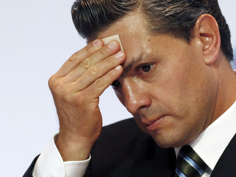 Mexico's President Enrique Pena Nieto wipes sweat from his brow during a signing ceremony among the Pacific Alliance at the Climate Change Conference in Lima, Peru, Wednesday, Dec. 10, 2014. Delegates from more than 190 countries are meeting to work on drafts for a global climate deal that is supposed to be adopted next year in Paris. (AP Photo/Juan Karita)